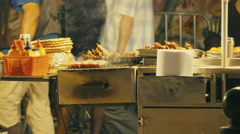 Fast food cart stand at street at night people passing by Stock Footage