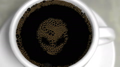Coffee bubbles in a white porcelain cup pop to reveal Alien face Stock Footage