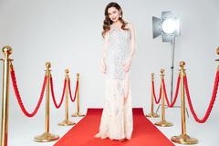 Charming woman walking on red carpet - stock photo