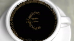 Coffee bubbles in a white porcelain cup pop to reveal a Euro symbol Stock Footage
