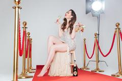 Woman holding heels and glass of champagne Stock Photos