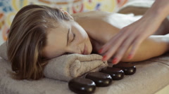Hot stone massage. Young woman having relaxing treatment Stock Footage