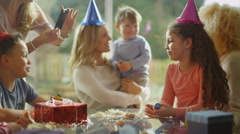 4K Little boy celebrating his birthday with a cake & happy family & friends Stock Footage