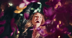 Happy young friends celebrating night life throwing colorful feathers Stock Footage