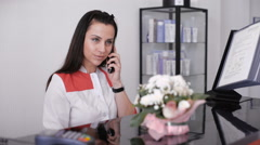 Portrait of a beautiful smiling nurse at desk station while talking on the phone Stock Footage