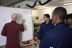Stock Photo of Mechanics teacher writing on board