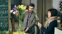 The young man is learning from a professional florist haw to work with flowers. Stock Footage