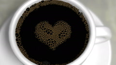Coffee bubbles in a white porcelain cup pop to reveal a love heart symbol Stock Footage