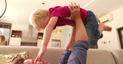 Father is playing with son  on sofa in Morning at Home Stock Footage