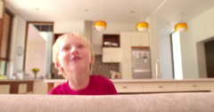 Little boy hides behind Couch and smiles in camera Stock Footage