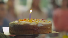 4K Little boy celebrating his birthday with a cake & happy family & friends - stock footage