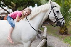 Smiling girl riding horse in yard Stock Photos