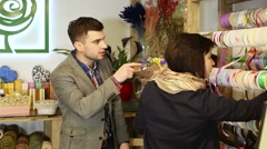 The client is choosing a decorative ribbon for a bouquet in the flower shop. Stock Footage