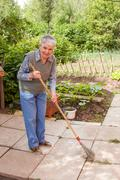 woman engages in cleaning up on lot land - stock photo
