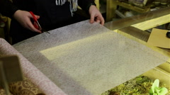 Florist is cutting paper with scissors for packing flowers. Stock Footage