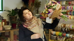 Florist is showing her customers a completed bouquet of flowers. - stock footage