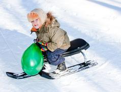a little boy in-field  on sledges - stock photo