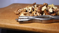 Walnuts are spinning on wood board. tongs for chopping nuts - stock footage