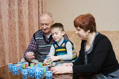 A grandmother and grand-dad play with a grandchild in blocks Stock Photos