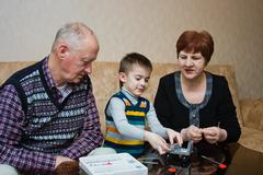 A grandmother, grand-dad, play with a grandchild in a designer Stock Photos