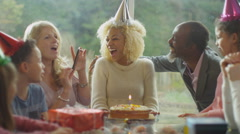 4K Happy woman celebrates her birthday with a cake & generations of family - stock footage