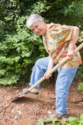 Elderly woman spades a vegetable garden Stock Photos