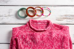 Pink wool pullover and bracelets. Stock Photos