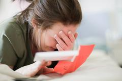 Crying teenage girl reading letter Stock Photos
