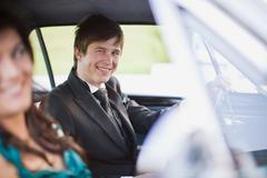 Teenagers driving car in formal wear Stock Photos