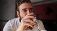 Young man with a beard drinking a glass of white wine Stock Footage
