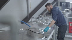 4K Worker in a brewery checking the equipment as he makes the product - stock footage