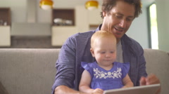 Modern Dad Taking Selfie with Infant Daughter on Couch Stock Footage