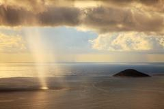 Rain shower and sun light beams through the dark clouds over the sea - stock photo