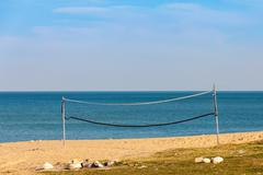 Old and neglected volleyball net on the beach. Stock Photos