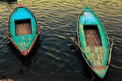 Colorful boats moored on Ganges river in Varanasi, India Stock Photos