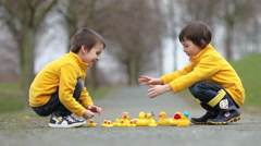 Two adorable children, boy brothers, playing in park with rubber ducks, havin Stock Footage