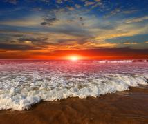 Majestic sunset over ocean shore Stock Photos