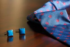 Cuff links and tie on mahogany wooden background Stock Photos