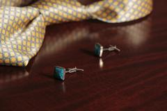 Cuff links and tie on mahogany wooden background - stock photo