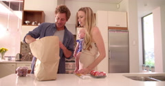 Family with Infant Daughter Unpacking Groceries in Kitchen - stock footage