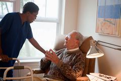 Nurse looking after senior man at home Stock Photos