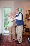 Senior couple dancing together in living room Stock Photos