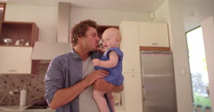 Modern Dad Holding and Kissing Infant Daughter on Cheek - stock footage