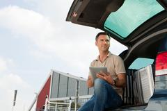 Stock Photo of Man using data tablet in airport carpark