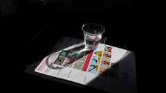Plastic glass with water stand on safety instructions, airliner cabin table Stock Footage
