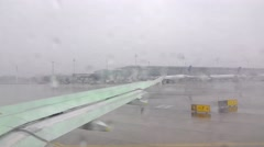 Aircraft taxiing to runway, green defroster dispersed on wing, cold weather Stock Footage