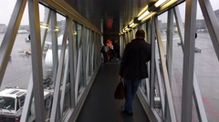 Come to aircraft, pass through glass walled aerobridge, people stand at end - stock footage