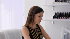 Beautiful brunette doing a manicure in a bright room Stock Footage