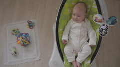 Happy Little Cute Baby Girl Swing in Electric Chair Bouncer  Top View Stock Footage