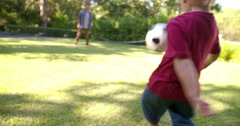 Modern Dad and Little Boy Playing Ball, Barefoot, in Garden Stock Footage